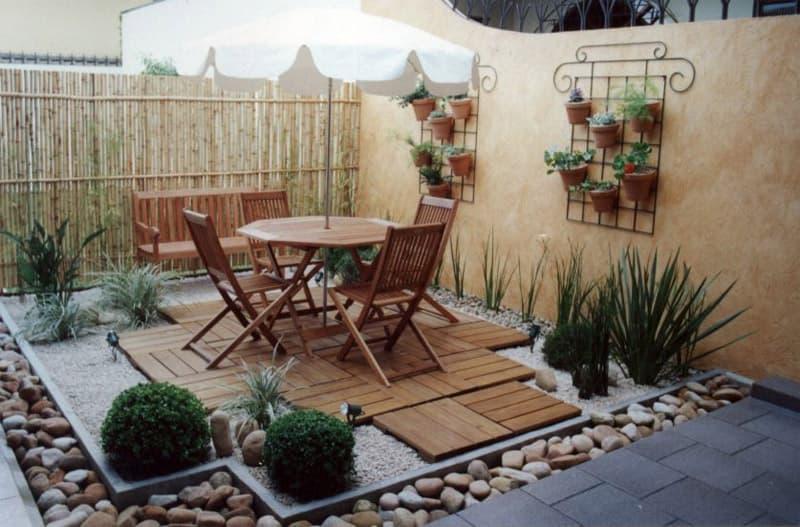 decoração de jardim simples com mesa e pedras