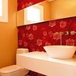 Belo papel de parede floral em tom sobre tom aplicado apenas em uma das paredes do lavabo
