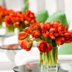 Use arranjos de flores vermelhas para decorar as mesas