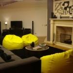 As cores cinza e amarelo decoram uma sala descolada, explorando o efeito dos puffs.