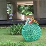 Uma esfera de garrafas verdes decora o gramado na época de natal.