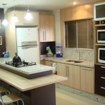 A mobília da cozinha planejada procura aproveitar o espaço vertical (paredes)