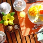 Frutas e flores deixam a mesa do café da manhã mais colorida.