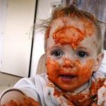 Bebê faz a festa com o molho de macarrão.