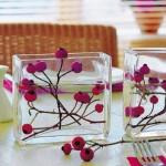 Galhos secos com cerejas dentro de recipientes com água. Enfeites simples, mas que fazem a diferença.