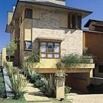 Sobrado com fachada moderna e revestimento nas paredes.