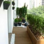 Chão de madeira e projeto de paisagismo deixam a varanda pequena um charme.