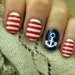 Unhas navy com listras brancas e vermelhas.