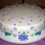 Bolo redondo decorado com rosas lilás de vários tamanhos e folhas verdes (Foto: divulgação)