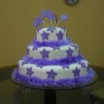 Bolo branco com decoração de estrelas lilás em pasta americana e plumas (Foto: divulgação)