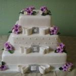 Bolo quadrado em camadas decorado com laços e flores lilás (Foto: divulgação)