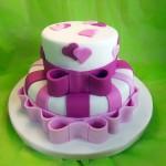 Bolo branco decorado com corações e laços em pasta americana, em dois tons de rosa (Foto: divulgação)
