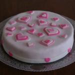 Bolo branco decorado com corações rosas de vários tamanhos (Foto: divulgação)