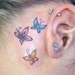 Tatuagem de borboletas coloridas atrás da orelha (Foto: divulgação)
