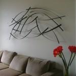 A escultura de parede é o plano de fundo do sofá. (Foto:Divulgação)