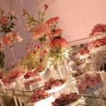 Flores rosas decoram a mesa de vidro junto com os doces. (Foto:Divulgação)