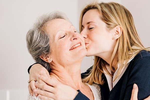 Mensagens para Dia das Mães filha beijando a mãe