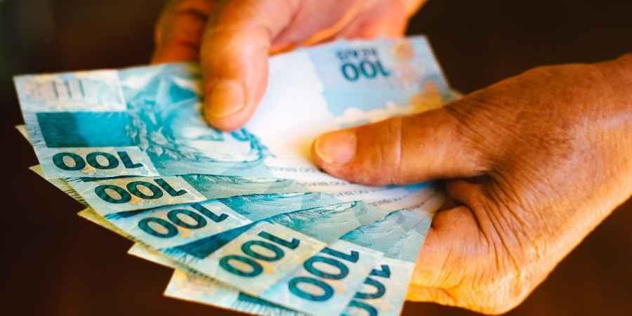 Homem segurando dinheiro receber auxilio