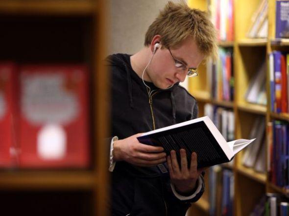 318690 size 590 rapaz lendo livro fone de ouvido biblioteca Lista de livros sobre o natal