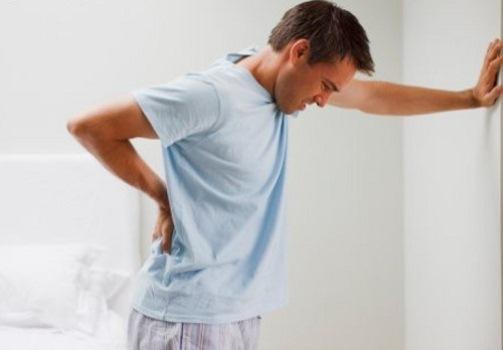 370930 Homem sentindo dor com mão na parede Como aliviar dores no nervo ciático