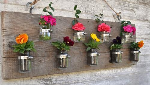 598840 Reutiliza%C3%A7%C3%A3o de vidros em jardim Como fazer 04 Reutilize vidros para fazer painéis com vaso de flores, que podem, inclusive, ser um suporte para guardar vários objetos.